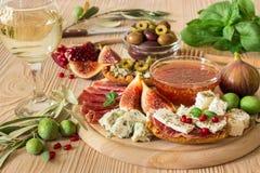 Köstlicher Aperitif für Wein auf hölzernem Brett Stockbild