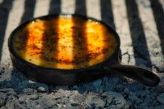 Köstlicher argentinischer Provolon-Garn-Käse Provoleta, der in einer Roheisenbratpfanne über der Glut und der Asche gekocht wird stockbild
