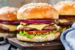 Köstlicher Burger auf hölzernem Brett Lizenzfreie Stockbilder