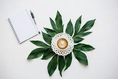 Köstlicher frischer Cappuccinokaffee in einem Becher mit schön gelegten Blättern nahe bei und einem Notizbuch für das Schreiben d Lizenzfreie Stockfotografie