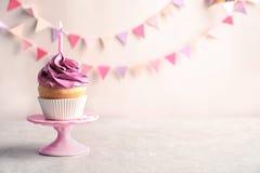 Köstlicher Geburtstagskleiner kuchen mit brennender Kerze Lizenzfreie Stockbilder