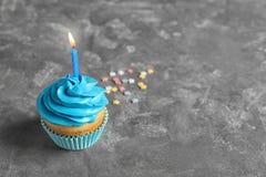 Köstlicher Geburtstagskleiner kuchen mit brennender Kerze Stockfotografie