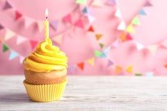 Köstlicher Geburtstagskleiner kuchen mit brennender Kerze Stockfoto