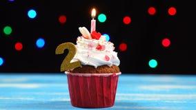 Köstlicher Geburtstagskleiner kuchen mit brennender Kerze und Nr. 2 auf mehrfarbigem unscharfem Lichthintergrund stock footage