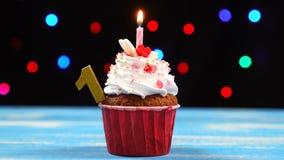 Köstlicher Geburtstagskleiner kuchen mit brennender Kerze und Nr. 1 auf mehrfarbigem unscharfem Lichthintergrund stock footage