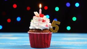 Köstlicher Geburtstagskleiner kuchen mit brennender Kerze und Nr. 5 auf mehrfarbigem unscharfem Lichthintergrund stock video