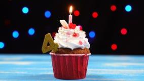 Köstlicher Geburtstagskleiner kuchen mit brennender Kerze und Nr. 4 auf mehrfarbigem unscharfem Lichthintergrund stock video