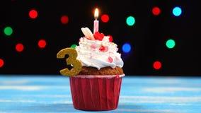 Köstlicher Geburtstagskleiner kuchen mit brennender Kerze und Nr. 3 auf mehrfarbigem unscharfem Lichthintergrund stock footage