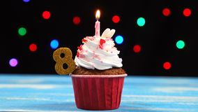 Köstlicher Geburtstagskleiner kuchen mit brennender Kerze und Nr. 8 auf mehrfarbigem unscharfem Lichthintergrund stock video footage
