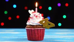 Köstlicher Geburtstagskleiner kuchen mit brennender Kerze und Nr. 44 auf mehrfarbigem unscharfem Lichthintergrund stock video footage