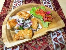 Köstlicher Grill auf einem hölzernen Brett mit Karotten stockfotos