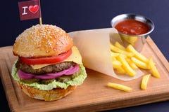 Köstlicher Hamburger mit Rindfleisch, Zwiebel, Kopfsalat, Tomate diente mit Kartoffelfischrogen und -ketschup auf hölzernem Brett Stockfoto