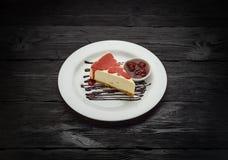 Köstlicher Käsekuchen mit Beeren auf einer weißen Platte über dunklem Holztisch Lizenzfreie Stockfotos