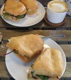 Köstlicher Kaffee mit einem belegten Brot mit Hühnerfleisch und einem Kopfsalat stockfotografie