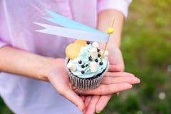 Köstlicher kleiner Kuchen mit blauer Creme und Eibischen in den Händen der Mädchen Süßes Geschenk für Geburtstag und Hochzeit Lizenzfreie Stockfotografie