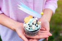 Köstlicher kleiner Kuchen mit blauer Creme und Eibischen in den Händen der Mädchen Süßes Geschenk für Geburtstag und Hochzeit Lizenzfreies Stockbild