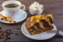 Köstlicher Kuchen auf einer Platte mit einer Gabel Weiße Schale mit schwarzem Kaffee und Zimtstangen nähern sich ihm Kaffeebohnen Lizenzfreies Stockfoto