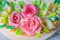 Köstlicher Kuchen mit Rosen, Lilie und Blättern auf hellblauem Holztischabschluß oben mit selektivem Fokus Lizenzfreies Stockfoto