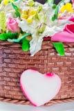 Köstlicher Kuchenkorb mit verschiedenen Blumen und dekorativem Herzen stockfotos