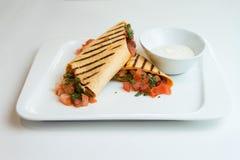 Köstlicher mexikanischer Burrito mit Fleisch, gelbem Pfeffer und Frühlingszwiebeln auf einer roten Tischdecke Stockbild