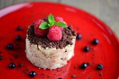 Köstlicher Nachtisch mit frischen Himbeeren und Schokoladensplittern auf einer roten Platte Unscharfer Hintergrund Stockfoto