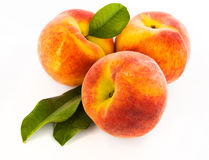 Köstlicher Pfirsich drei mit grünen Blättern Lizenzfreies Stockfoto