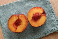 Köstlicher Pfirsich geschnitten zur Hälfte Stockfotografie