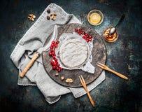 Köstlicher reifer Camembertkäse auf hölzernem Schneidebrett mit Beeren und Soße auf rustikalem Hintergrund, Draufsicht Stockbild