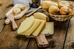 Köstlicher reifer Käse mit knusperigem Stangenbrot und Wein Stockbilder