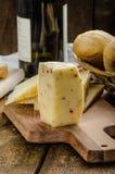 Köstlicher reifer Käse mit knusperigem Stangenbrot und Wein Lizenzfreie Stockfotos