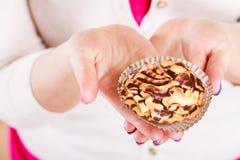 Köstlicher süßer kleiner Kuchen in den menschlichen Händen gluttony stockbild