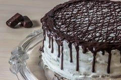 Köstlicher Schokoladenkuchen mit sahniger Creme und Pralinen Stockbild