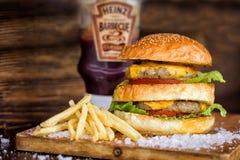 Köstlicher selbst gemachter Maxi Burger mit gegrilltem Rindfleischsteak, Kopfsalat, Käse, Tomate, Zwiebel, Barbecue-Soße, Honigse stockfotografie