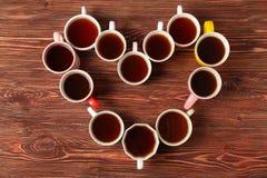Köstlicher Tee in den Schalen, die Herz bilden Stockfotografie