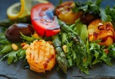 Köstlicher warmer Salat des Kopfsalates, des Spargels, der Kamm-Muscheln mit Oliven, der Tomaten, der Zitrone, der Kiefernnüsse u Stockfoto