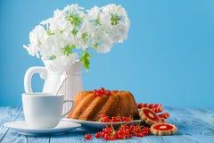 Köstlicher Zitronenkuchen auf blauem Hintergrund mit Beeren und Blumen Stockbild
