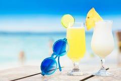 Köstlicher zwei Fruchtcocktail und Sonnenbrille durch den Strand Lizenzfreie Stockbilder