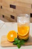 Köstliches Auffrischungsgetränk des Bechers der orange Frucht, hineingegossenes Wasser Lizenzfreies Stockbild