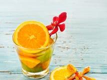 Köstliches Auffrischungsglasgetränk der Mischung trägt Orange und Zitrone auf blauem hölzernem, Infusionswasser Früchte Stockfotos