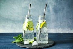 Köstliches Auffrischungswasser mit Gurke in den Flaschen stockfotografie