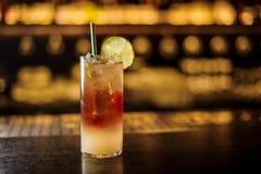 Köstliches dunkles stürmisches Cocktail verziert mit Kalkscheibe auf dem Barzähler stockbilder