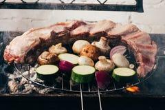 Köstliches Fleisch mit dem Gemüse, das auf Grill sich vorbereitet stockfoto