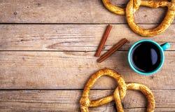 Köstliches Frühstück, eine Brezel mit Kaffee auf hölzernem Hintergrund Das Lebensmittel, die Getränke Lizenzfreies Stockfoto