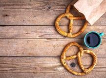 Köstliches Frühstück, eine Brezel mit Kaffee auf hölzernem Hintergrund Das Lebensmittel, die Getränke Stockbild