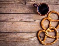 Köstliches Frühstück, eine Brezel mit Kaffee auf hölzernem Hintergrund Das Lebensmittel, die Getränke Lizenzfreies Stockbild