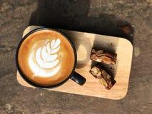 Köstliches Frühstück; Lattekunstkaffee in der schwarzen Schale und im Schokoladenkuchen überstieg mit der geschnittenen Mandel stockfotos