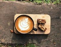 Köstliches Frühstück; Lattekunstkaffee in der schwarzen Schale und im Schokoladenkuchen überstieg mit der geschnittenen Mandel lizenzfreie stockbilder