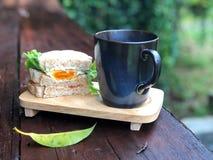 Köstliches Frühstück mit frischem Sandwich und schwarzer Kaffeetasse auf dem Holztisch stockfoto