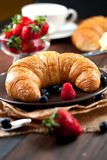 Köstliches Frühstück mit frischen Hörnchen und reifen Beeren auf altem hölzernem Hintergrund stockfoto