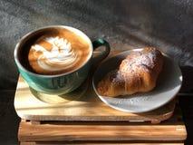 Köstliches Frühstück; Schwanform Latte-Kunstkaffee in der grünen und weißen Schale und im Hörnchen lizenzfreies stockfoto